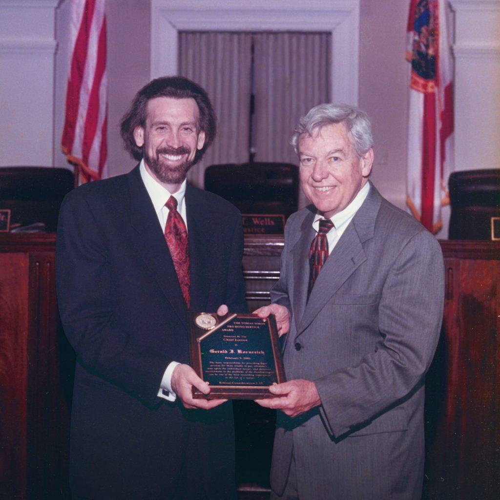 Gerald Kornreich receiving Tobias Simon pro bono service Award from the Florida Supreme Court